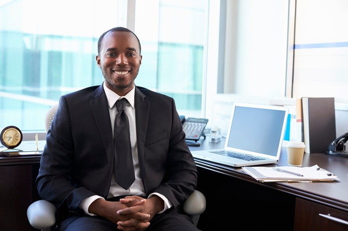 Smiling man in suit at a desk