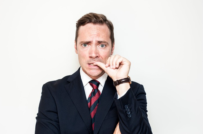 Man in a suit biting his thumbnail with a worried expression.
