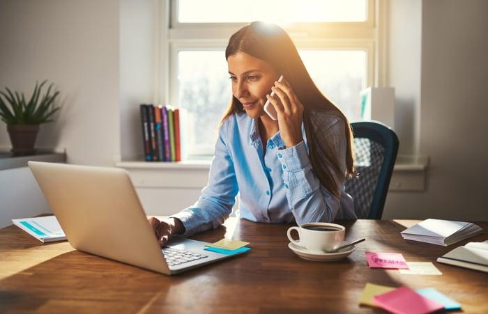 Woman at laptop talking on phone