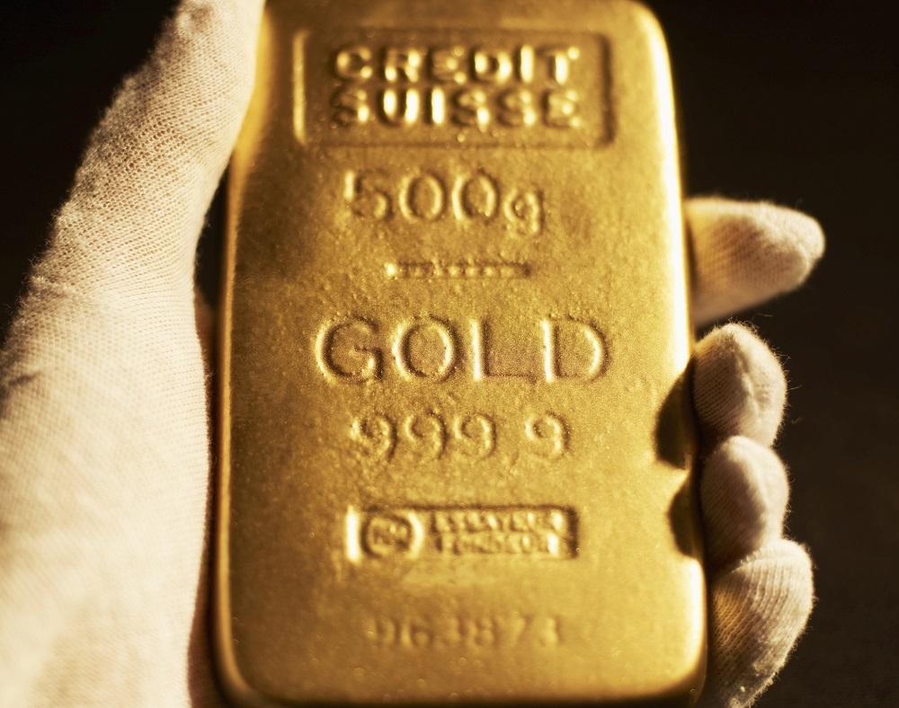 A gloved hand holding a gold bar