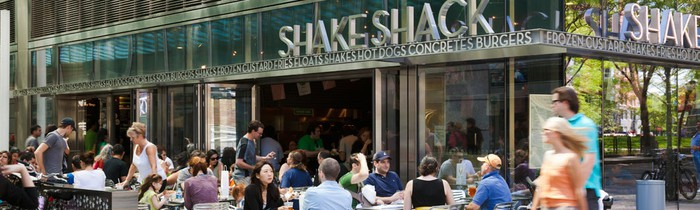 A crowd sitting at the patio outside of a Shake Shack.