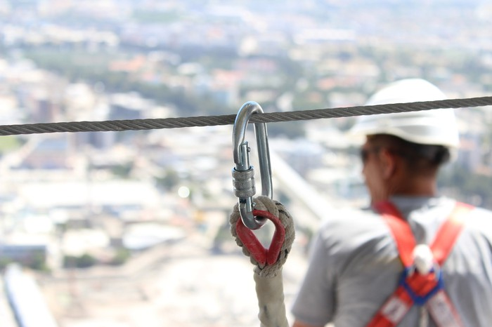 A construction worker connected to a safety line.