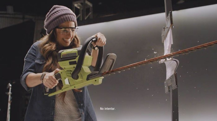 A woman with a chainsaw cutting her phone bill in half.