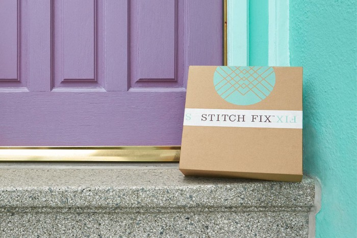 Box labeled Stitch Fix sitting on a doorstep of a teal blue house with a light purple door.