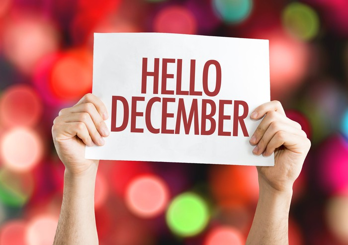 """Person holding up """"Hello December"""" sign in front of colored lights."""