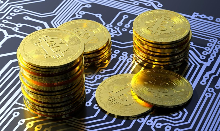 Several stacks of gold coins with the Bitcoin symbol on them sitting on a digital surface.