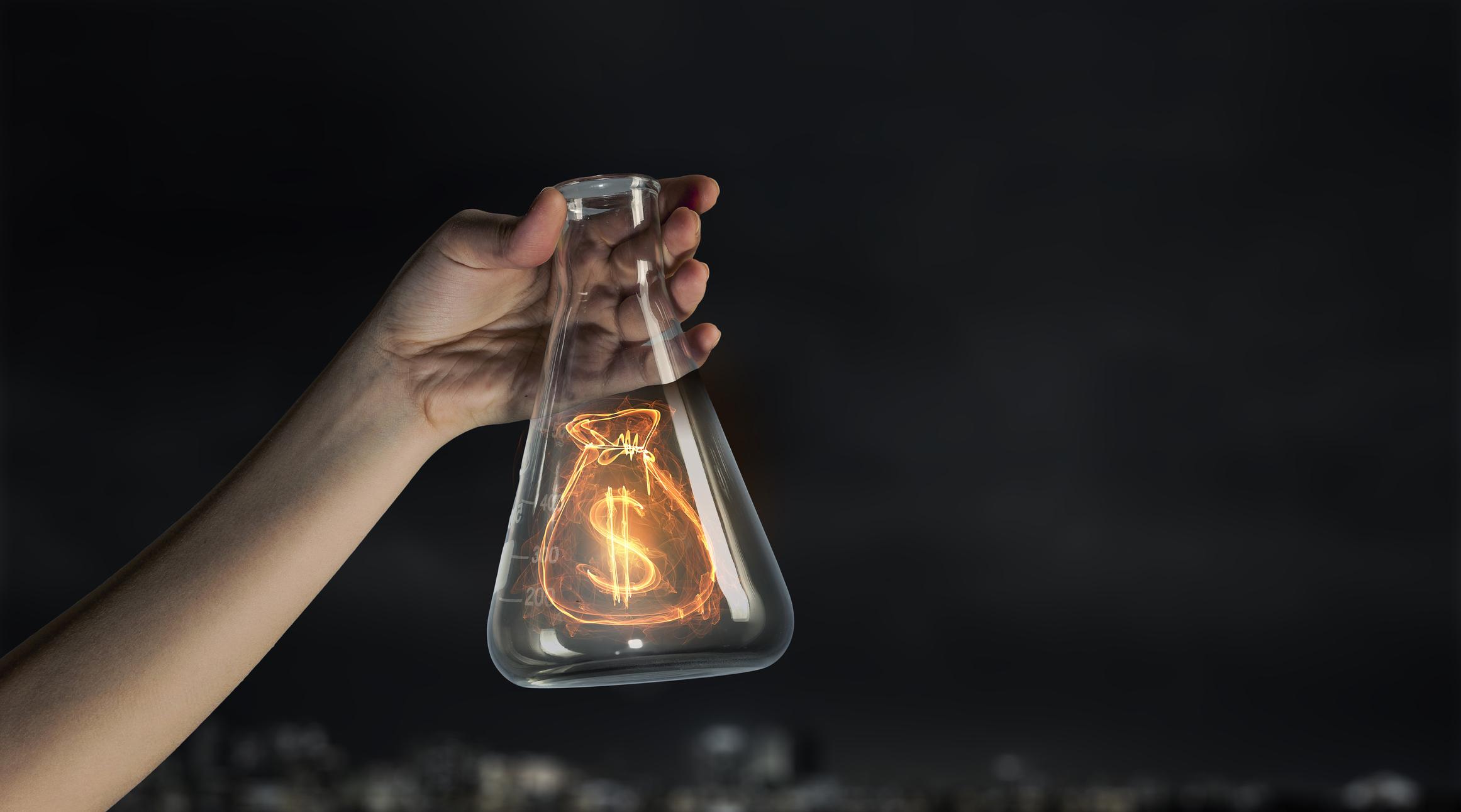 Lit up dollar sign inside of an erlenmeyer flask.