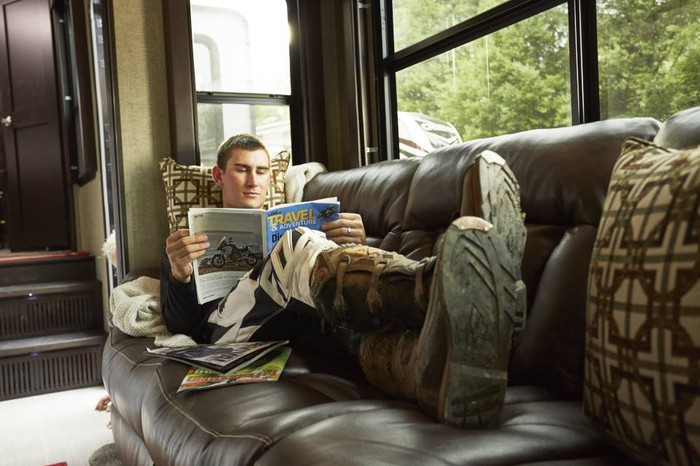 Person reading on a couch inside a recreational vehicle.