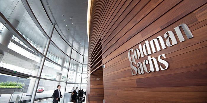 Lobby of a Goldman Sachs building, with glass outer walls and wood inner wall with company logo on it.