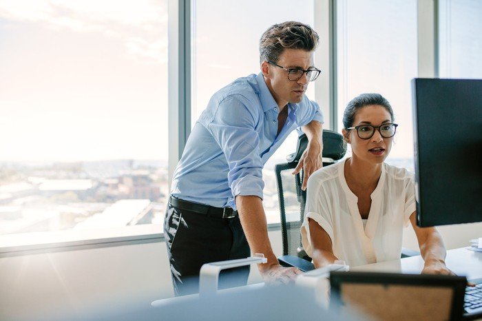 Two corporate colleagues looking at a computer screen