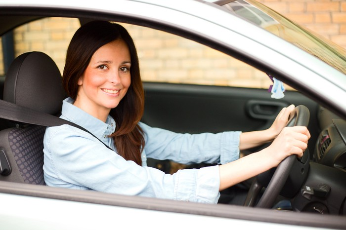 A woman is seen driving a car.