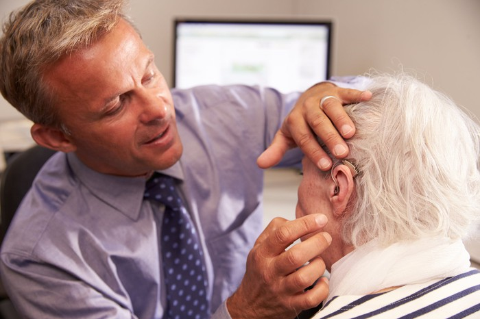 A man fits an elderly woman with a hearing aid.