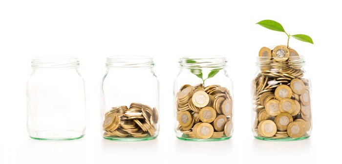 Four clear jars arranged in a row, representing growth. The first is empty, the second is partially filled with coins, the third has more coins and a green sprout, and the fourth is overflowing, with the sprout sticking out the top.