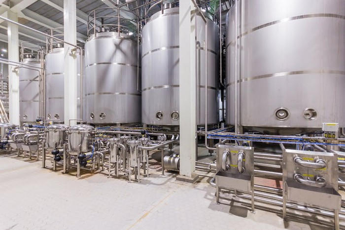 Stainless steel tanks in a biomanufacturing facility.