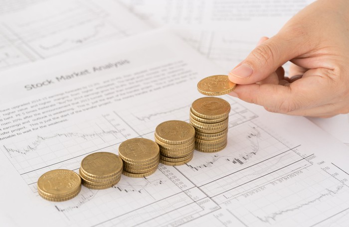 Five stacks of coins, ascending in size from right to left with a hand placing a coin on the last stack on the right.