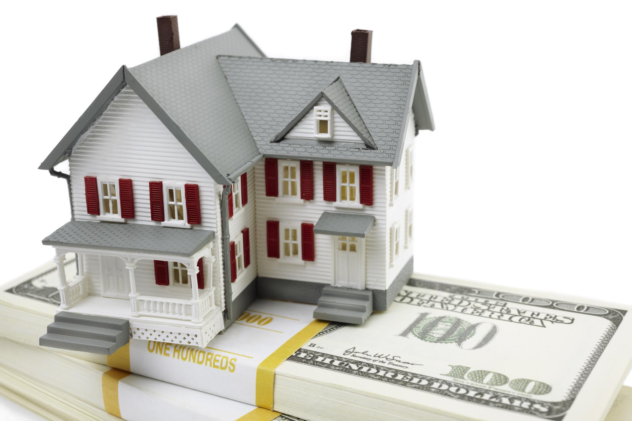 A model of a house sits atop bundles of U.S. $100 bills.