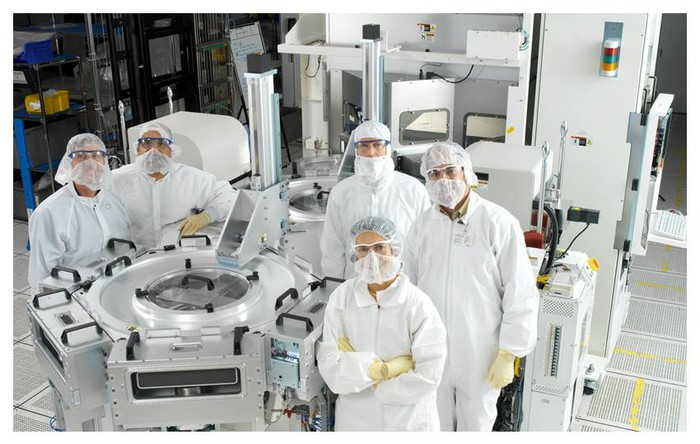 Semiconductor workers pose for a picture in a clean room.