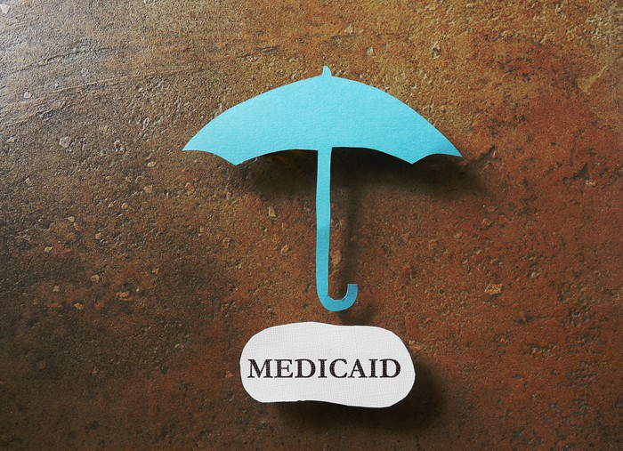 A paper umbrella above a piece of paper with Medicaid written on it.