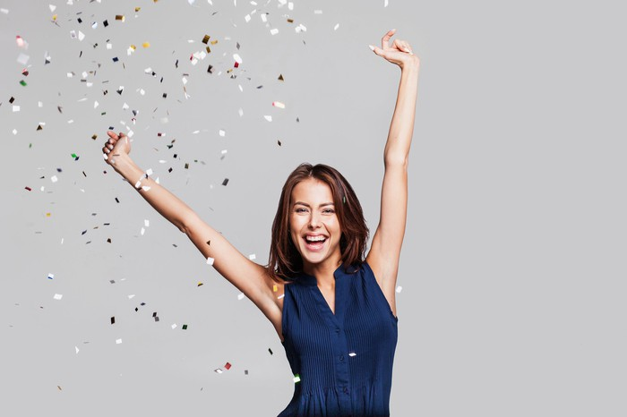 A smiling woman with arms raised and confetti falling around her.