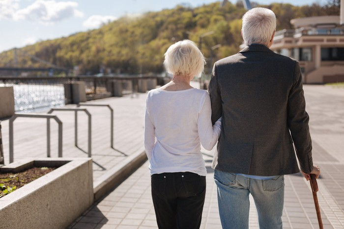 Elderly couple walking along a river