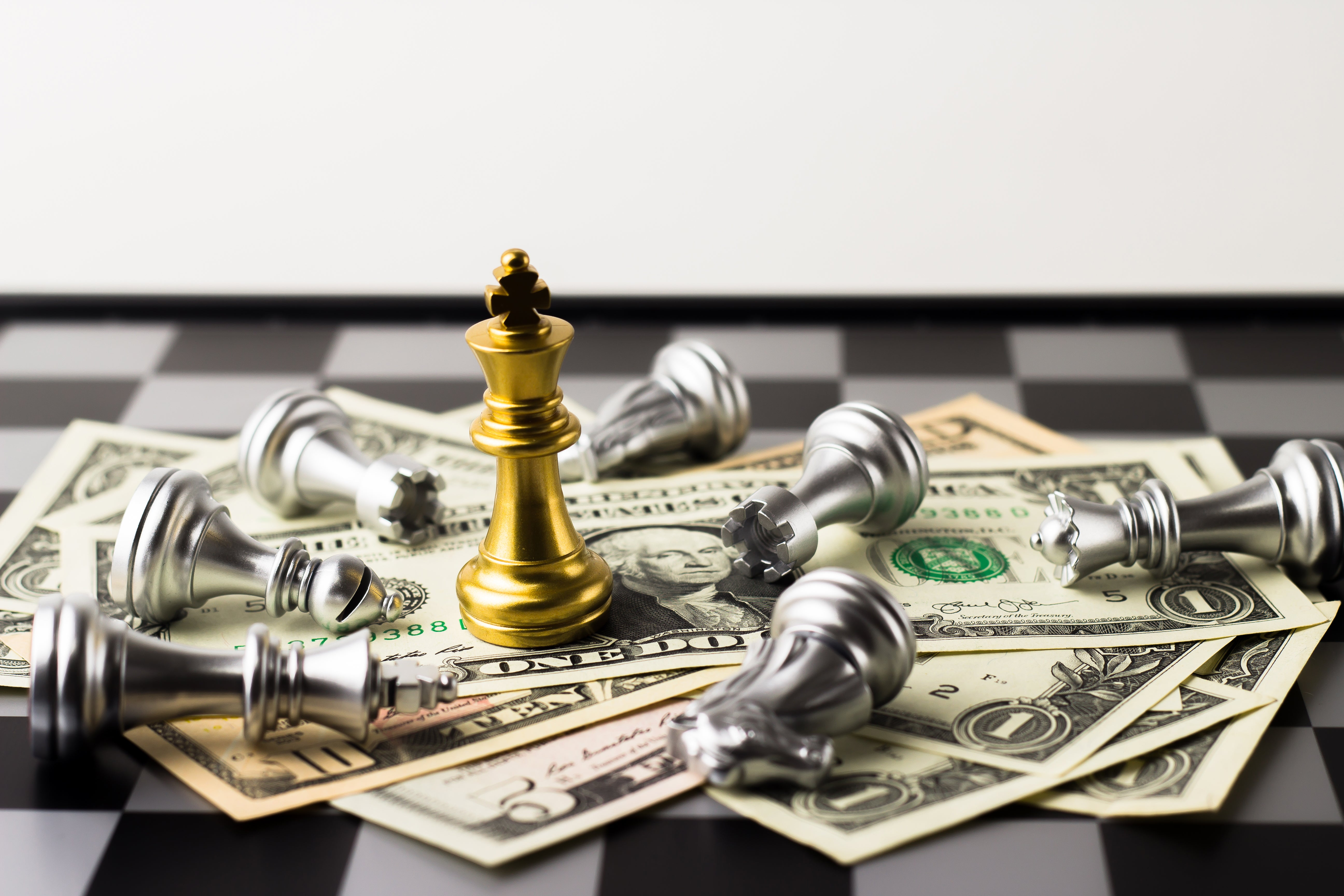 Chess pieces and cash on a chess board with king on top of cash.