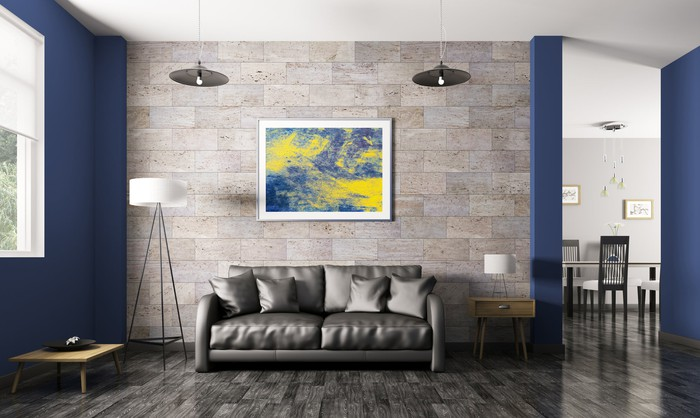 A blue and yellow painting hanging above a dark gray couch