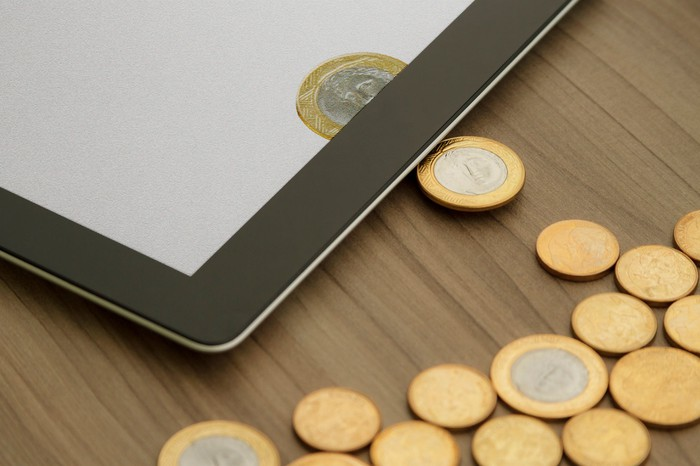 Physical coins on a table being transformed into digital currency on a tablet.