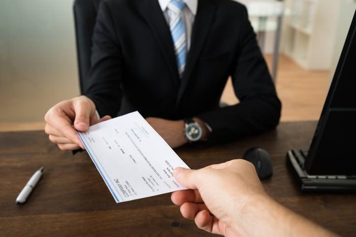 A businessman handing a paycheck across the desk to an employee.