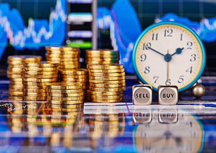 "A pair of dice say ""buy"" and ""sell"" beside a clock and stacks of gold coins."