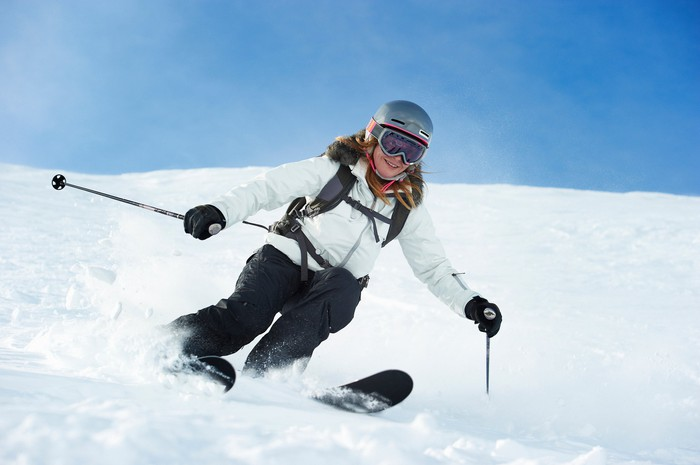 A skier heads down a snowy slope.
