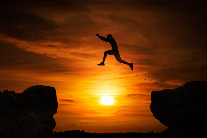 Silhouette of a man jumping over an abyss at sunset.