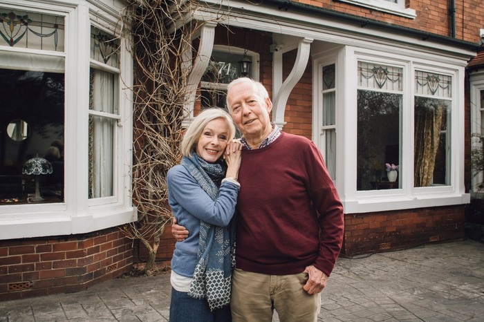 senior man and woman smiling and holding each other in front of a house