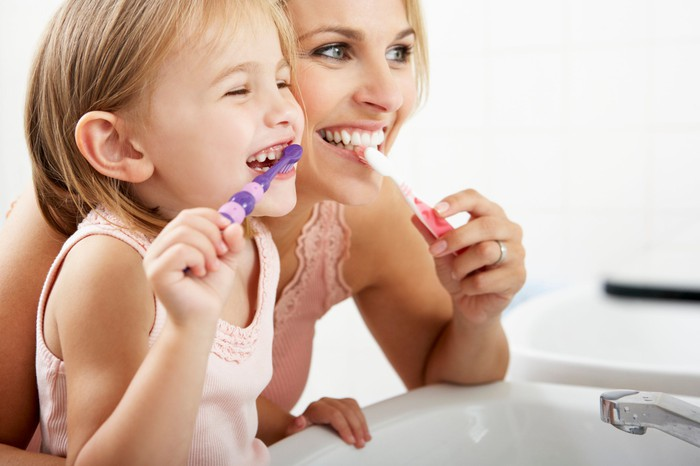 A mom and daughter smile while brushing their teeth.