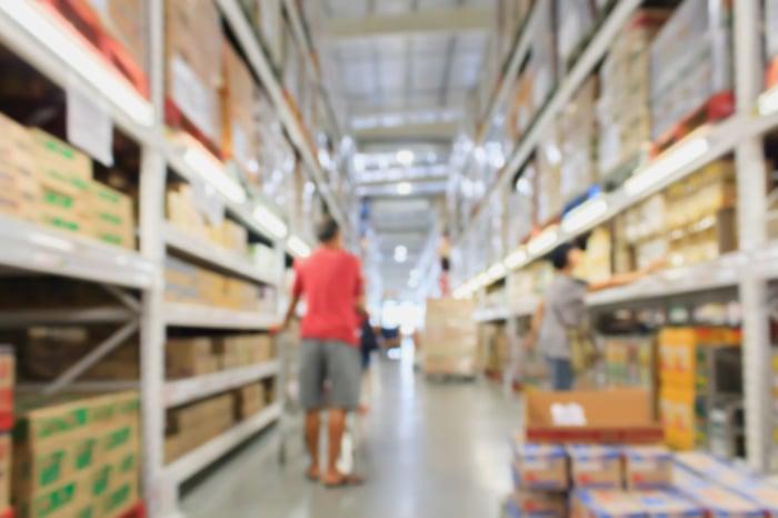 A shopper moves through an aisle at a warehouse retailer.