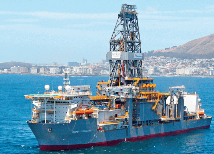 A rig drillship leaves port for the open sea.