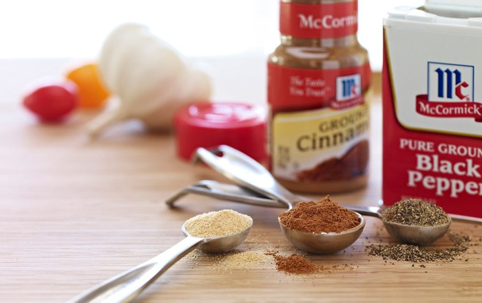 McCormick cinnamon and pepper bottles next to measuring spoons filled with spices