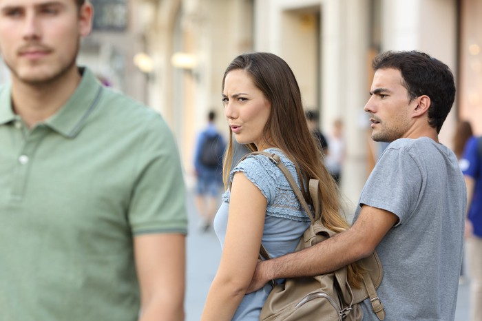 Woman walking with her boyfriend turns around to look at another man.