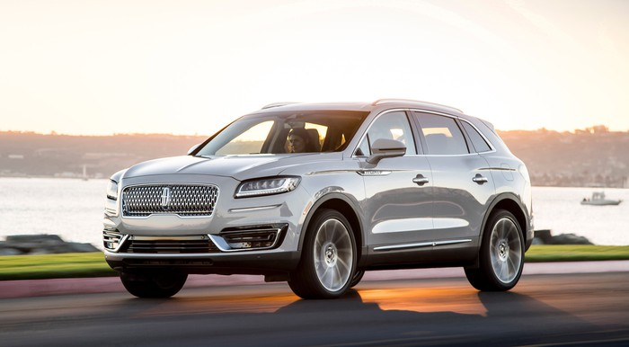 A silver 2019 Lincoln Nautilus, a midsize crossover SUV, on a waterfront road.