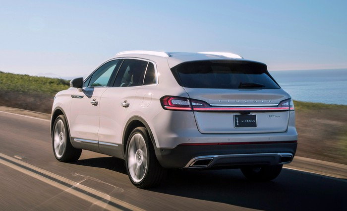 A view of the rear of a 2019 Lincoln Nautilus driving on a coastal road.