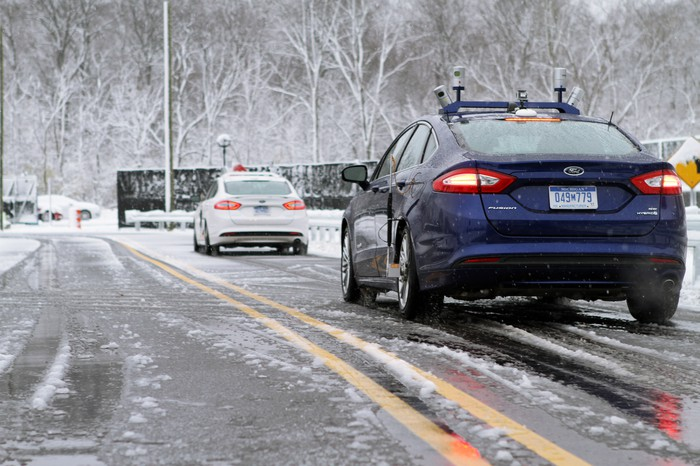 2 Ford Fusions with visible self-driving hardware are shown testing on a snowy road.