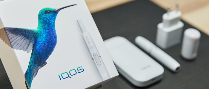 iQOS packaging with heating system, cigarette shape, plug, and accessories on a table.