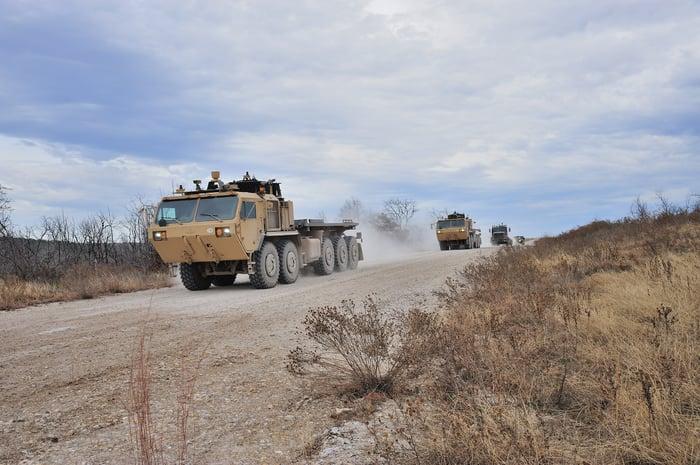 A autonomous driving military vehicle leading a convoy.