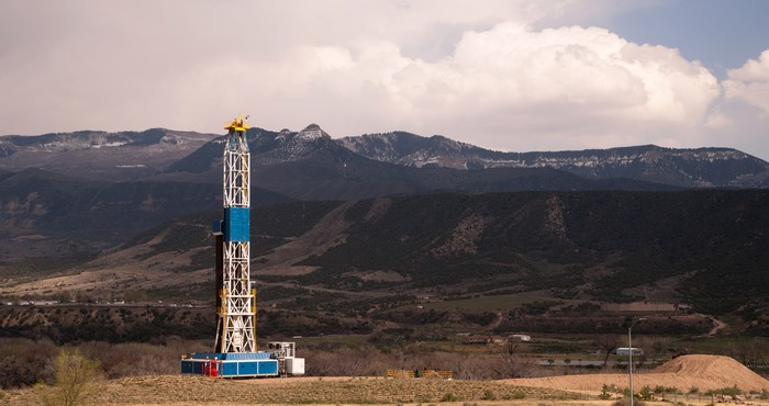 Drilling rig at work with mountains in background.