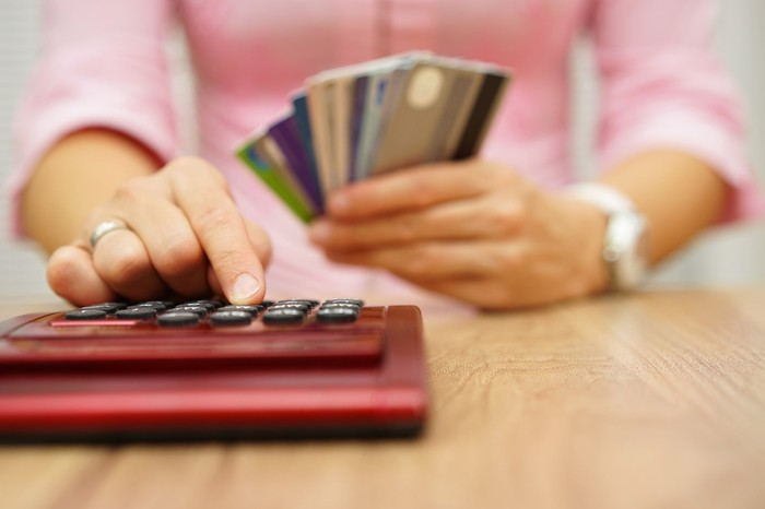 Woman holding credit cards while using a calculator