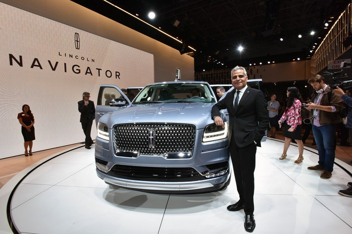Galhotra is standing on Lincoln's auto-show stand with a Navigator SUV.