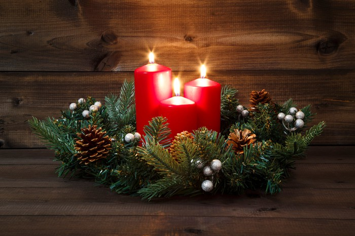 Three red candles lit in the center of a wreath of evergreen branches and pine cones.