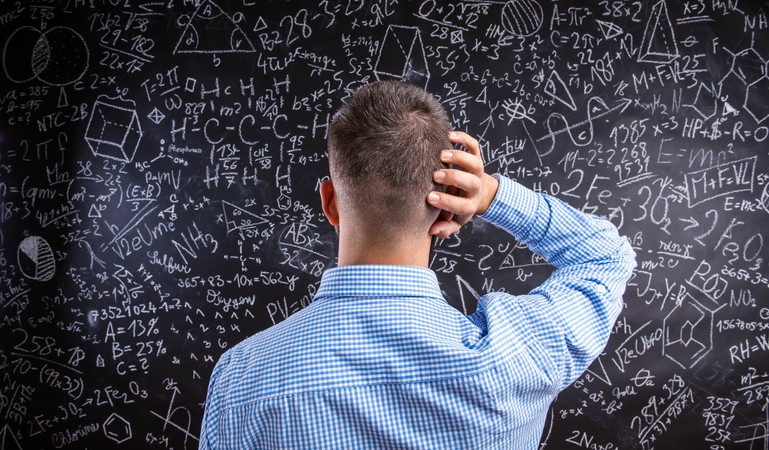 confused man staring at blackboard with complicated equations formulas math