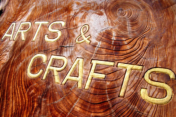 Arts and crafts written in gold on a roughly hewn piece of wood.
