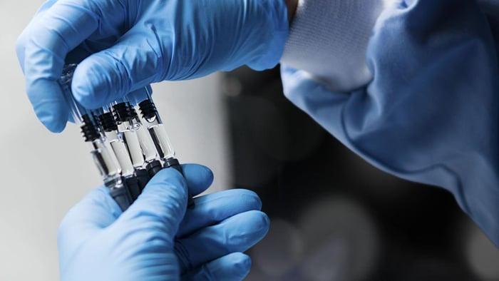 Pfizer scientist holding vials.
