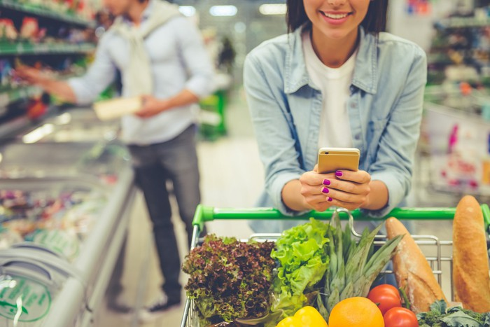 A young woman buys groceries and uses her smartphone